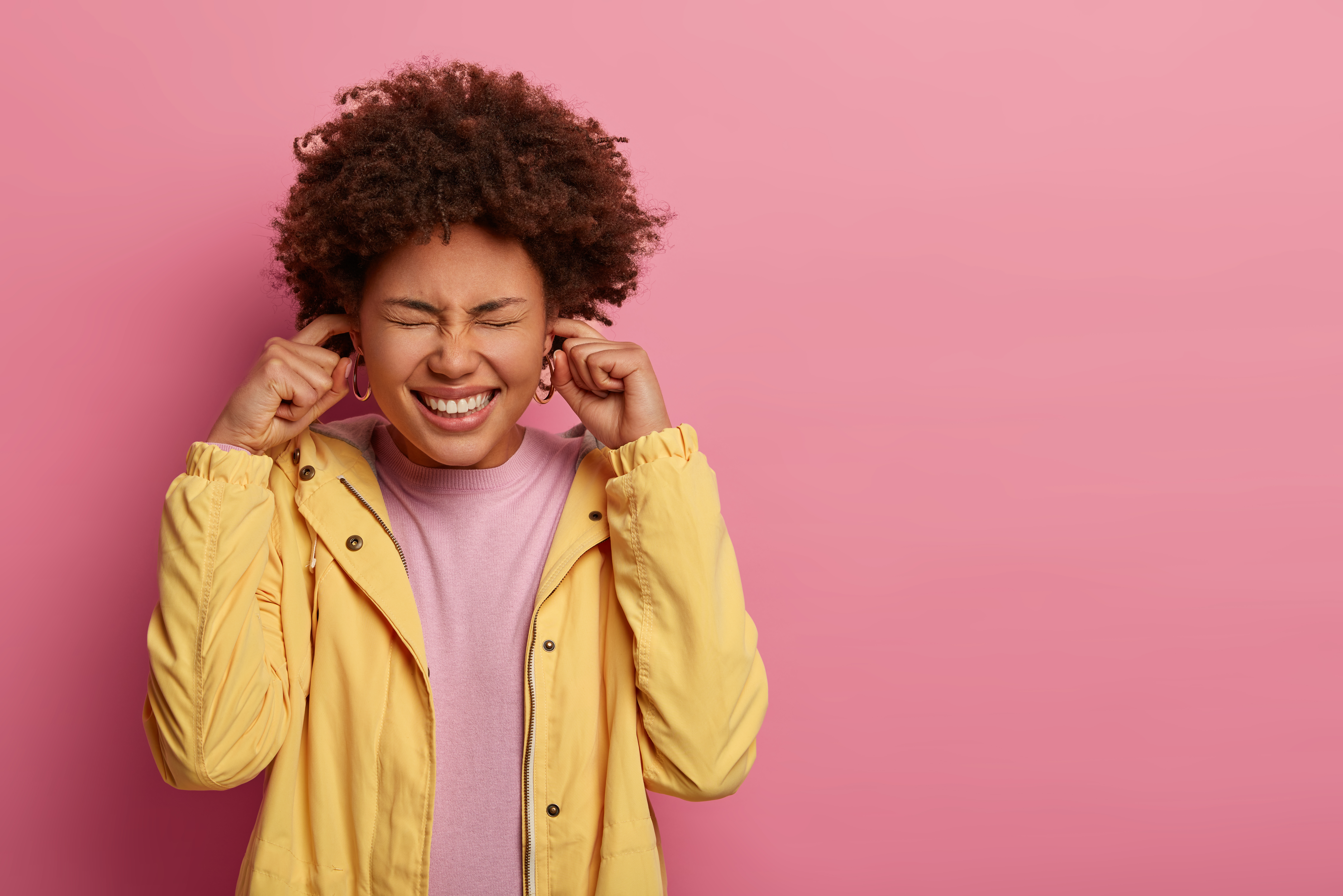 Studio shot of displeased dark skinned woman plugs ears, squints face and ignores unpleasant sound, clenches teeth, wears yellow anorak, stands over rosy wall, free space for your promotional content