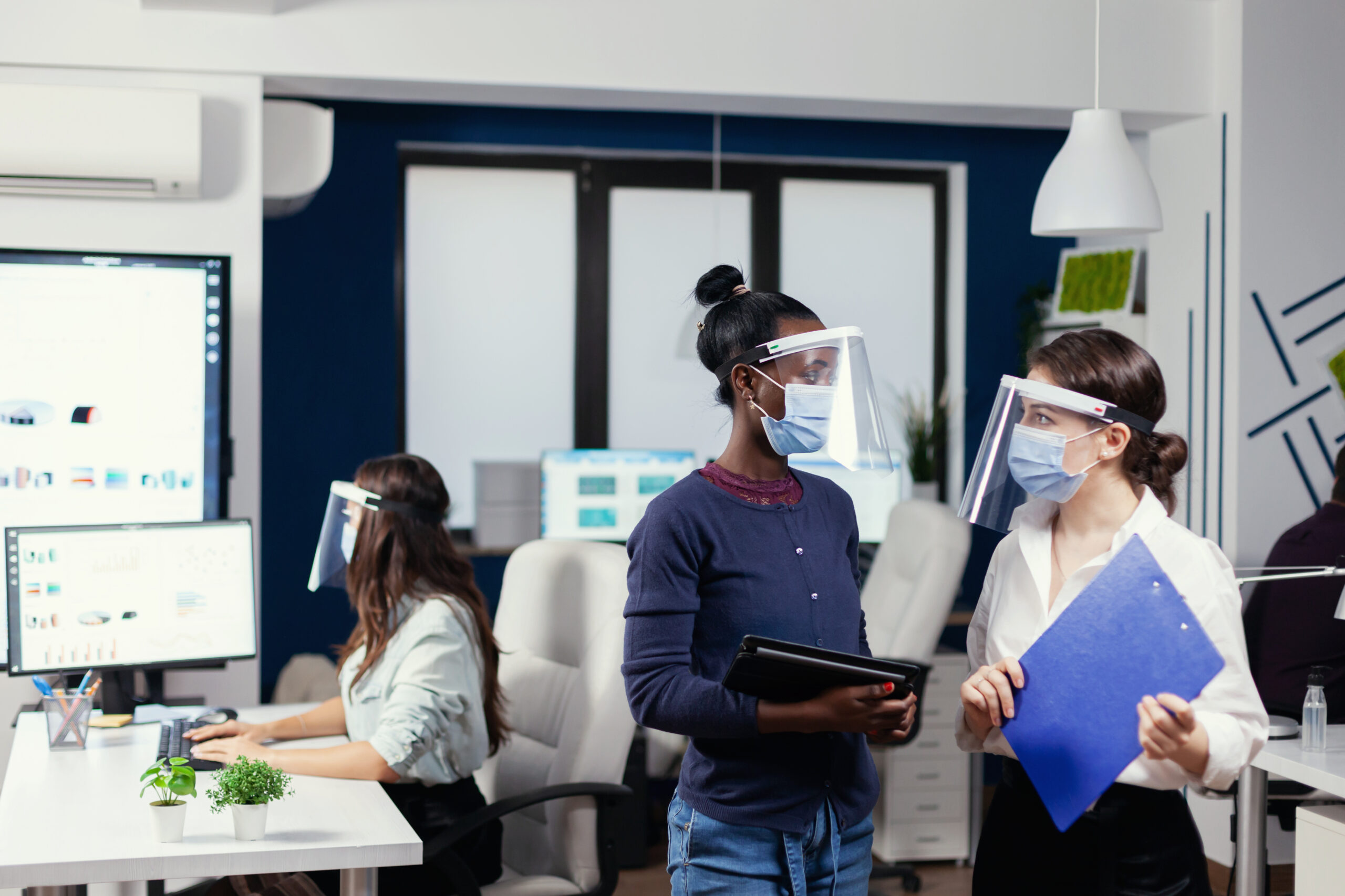 African and caucasian coworkers discussing statistics in workplace wearing face mask. Multiethnic business team working respecting social distance during global pandemic with coronavirus.