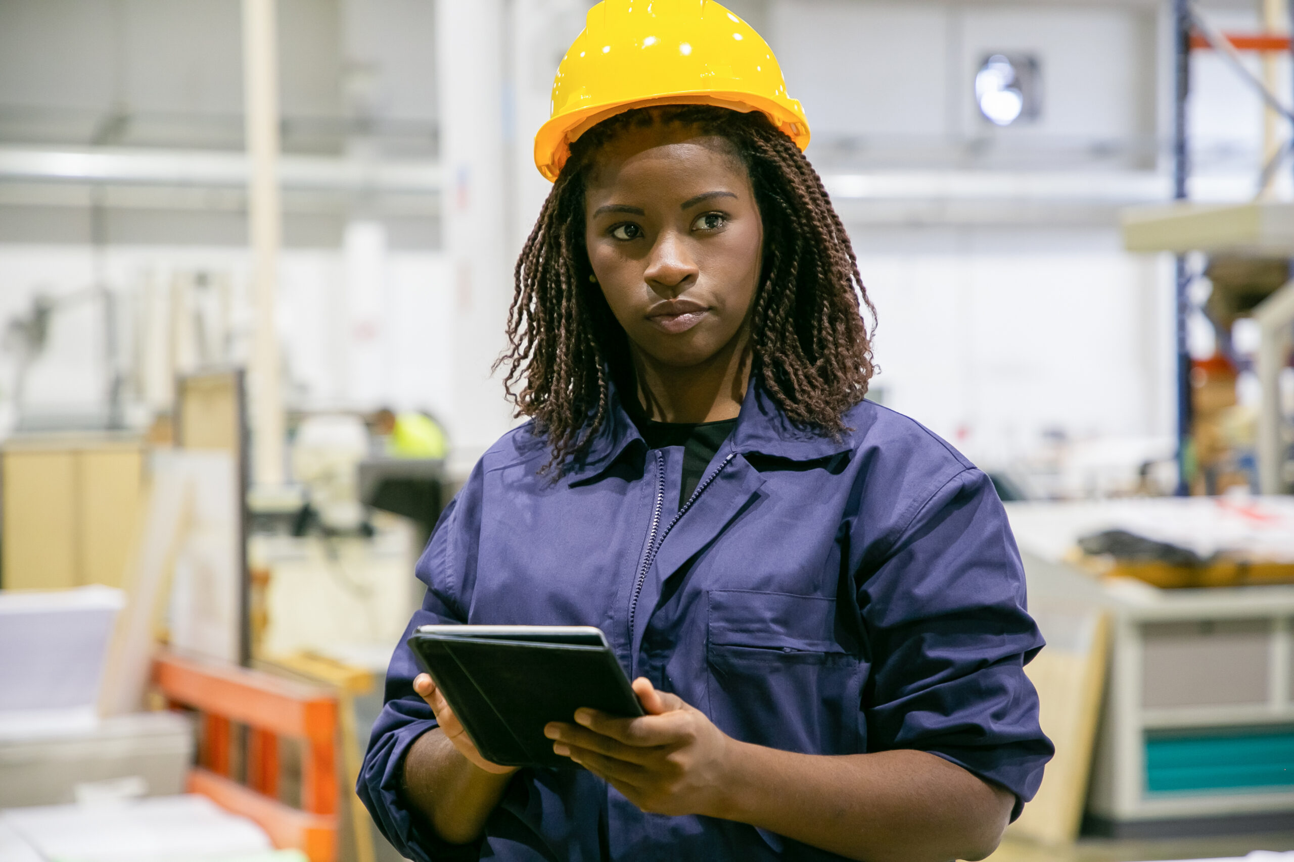 Content female plant worker standing with tablet and looking away. Portrait of pensive African American woman doing her job, thinking and wearing uniform. Manufacture and digital technology concept